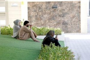 Afghani evacuees sit in a park and talk to their families back home, at a temporary residence compound in Doha, Qatar, August 27, 2021